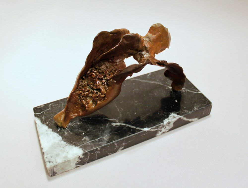 Abstract bronze sculpture mounted on dark polished stone slab