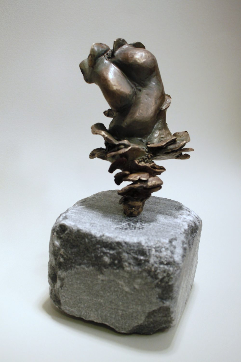 Abstract bronze sculpture reminiscent of female torso and waves, on stone cube base
