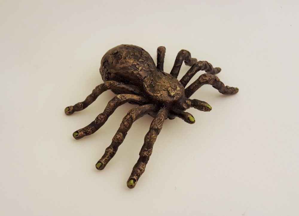 Bronze sculpture of spider with nails painted green