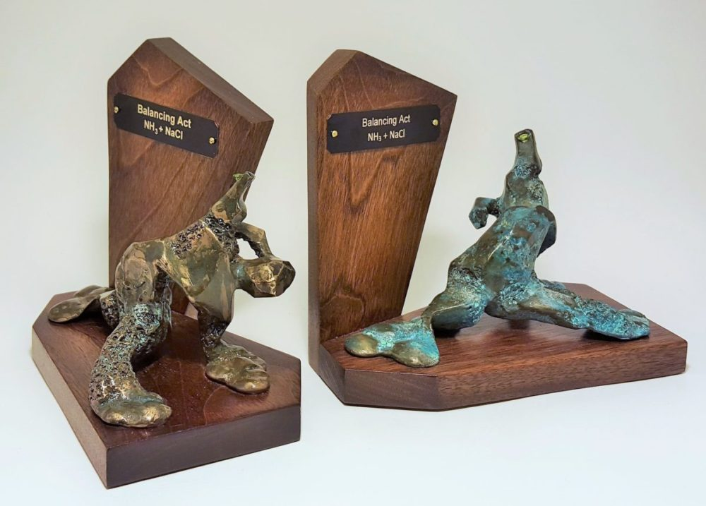 Two abstract bronze sculptures forms on wood bookends