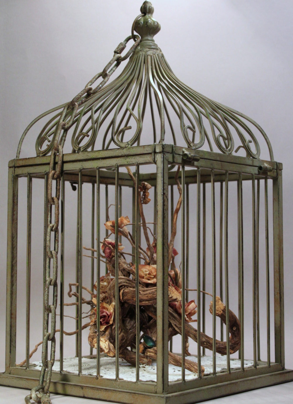 Dried roses arranged in a metal bird cage