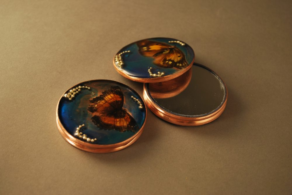 Three round mirrors with copper edges. Butterfly in resin on top with blue background.