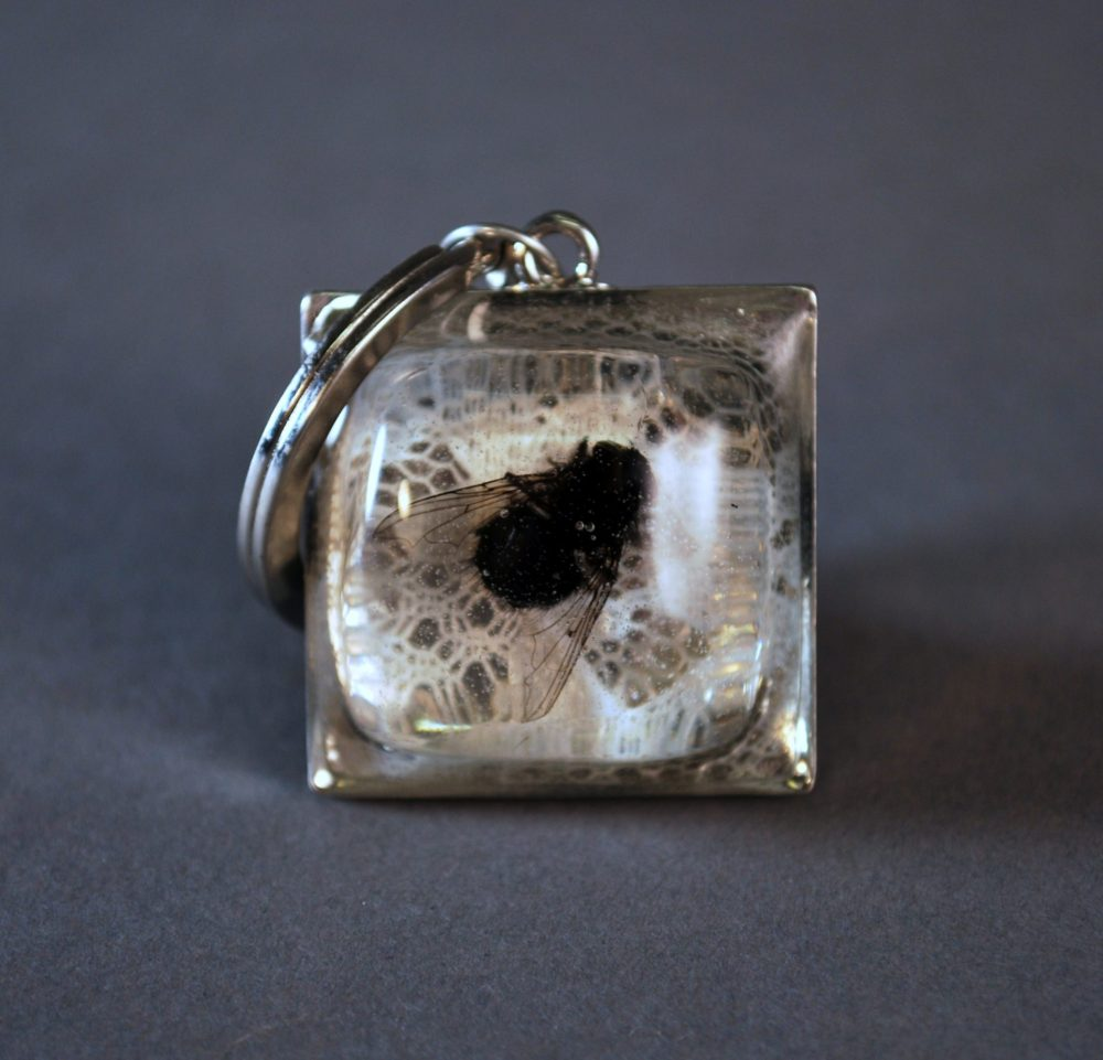 Keychain with fly set in resin on lace background