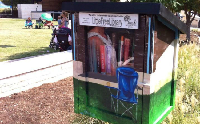 Blue lawn chair and amphitheater painted on little library box containing books.
