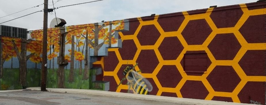 Mural on exterior wall of honeycomb pattern and giant bee next to fall trees