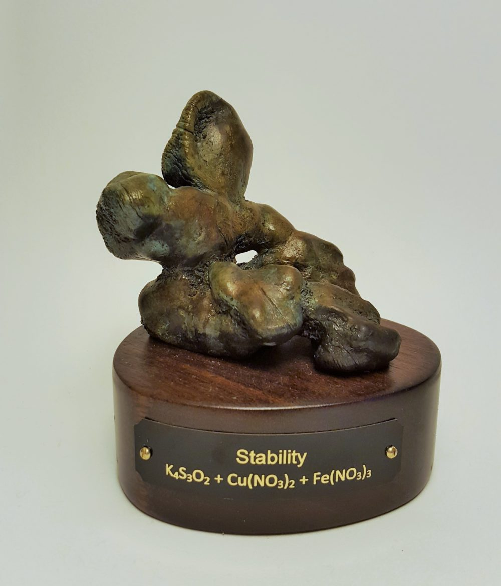 Abstract bronze sculpture on cylindrical wood base with plaque labeled Stability and K4S3O2 + Cu(NO3)2 + FE(NO3)3