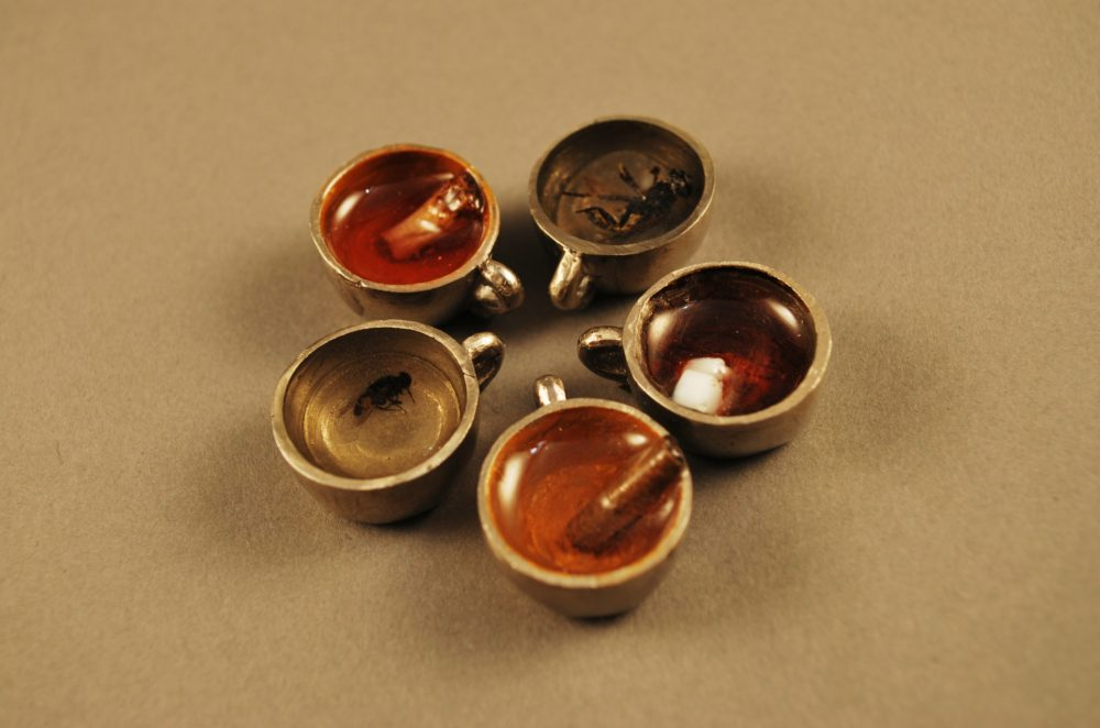 Five tiny teacups containing an insect in resin of various colors