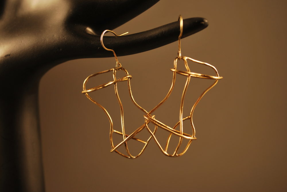 Gold colored earrings shaped into torso form