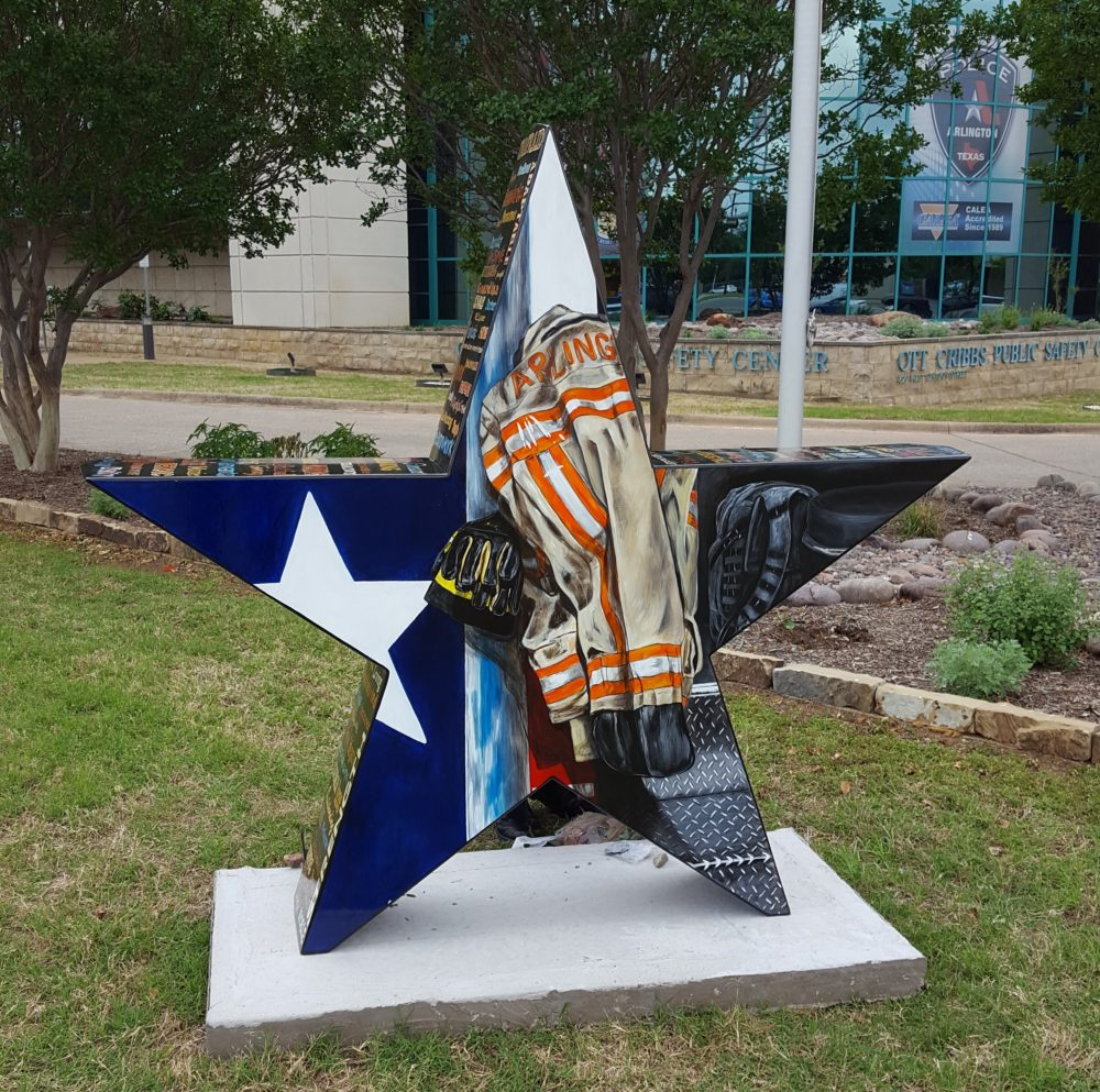 Firefighter jacket and Texas flag star painted on large star sculpture installed outdoors